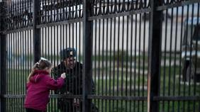 A Ukrainian soldier speaks to his daughter through a gate as he waits inside the Sevastopol tactical military brigade base near Belbek in Sevastopol on March 3, 2014. Russian forces have given Ukrainian soldiers an ultimatum to surrender their positions in Crimea or face an assault, a Ukrainian defence ministry spokesman said. 'The ultimatum is to recognise the new Crimean authorities, lay down our weapons and leave, or be ready for an assault,' said Vladyslav Seleznyov, the regional ministry spokesman for the Crimea.