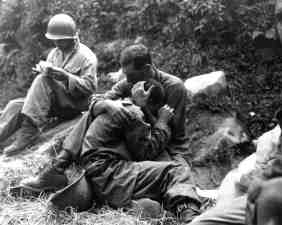 A grief stricken Infantry man in Korea is comforted by another soldier after his buddy died.