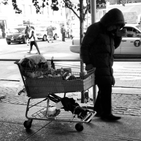 Homeless person pushing a shopping cart