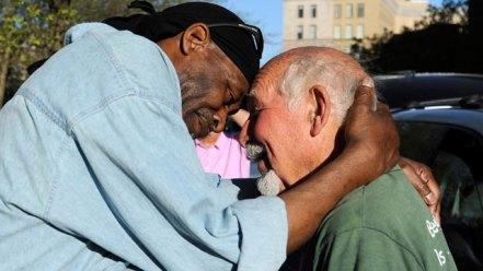 two homeless men hugging