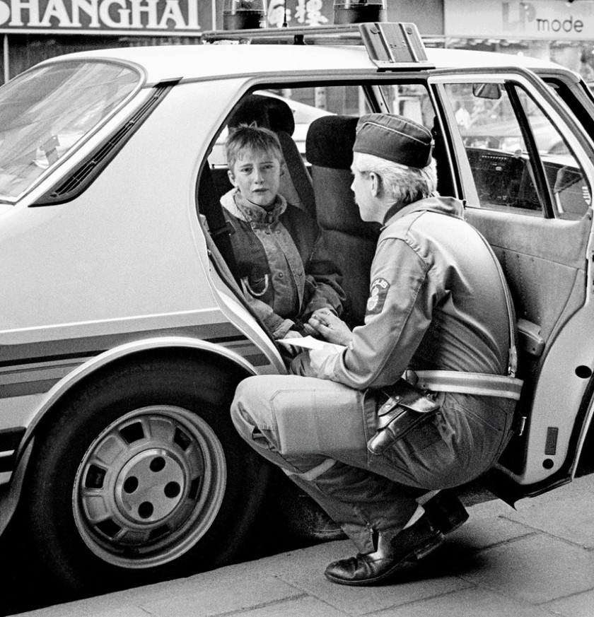 """Policeman comforts crying boy after he was hit by a car while skateboarding in Malmö, Sweden, 1986."""