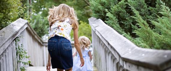 Woman walking over bridge with girl