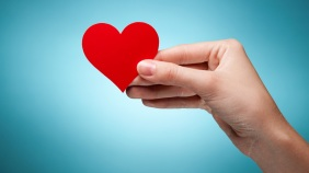 Woman's hand holding symbol - red heart. Against blue background