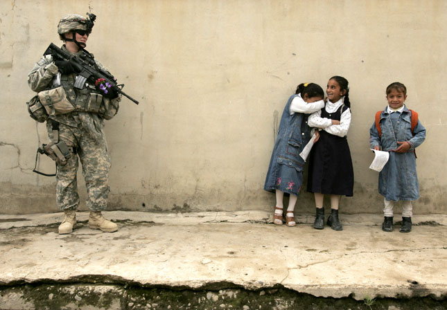 16 April, 2007. A girl becomes embarrassed after giving flowers to a female US soldier on duty in the northern Iraqi city of Mosul.