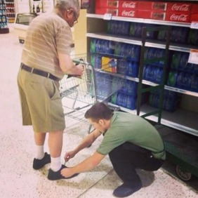 helping an elderly man tie his shoe