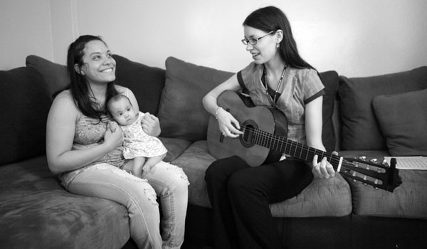 Meredith Traver playing guitar for 6-month-old Cecilia Havre and her mother, Chantel Vasquez. Cecilia has a genetic disorder called Trisomy 18, which claims half its victims before the first week of life.