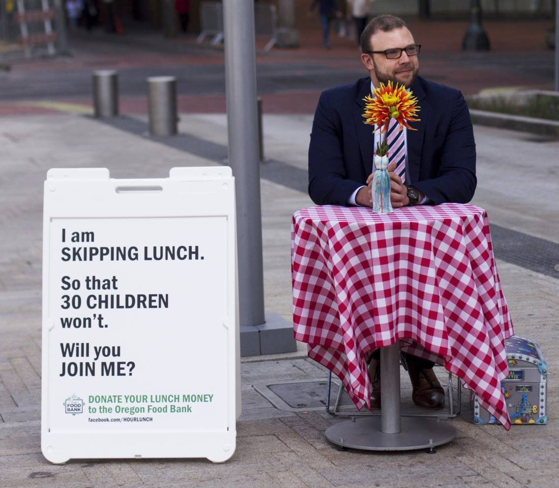 Portland man skips his lunch to raise money, awareness for Oregon Food Bank Anton Cobb, 32, sits alone in Director's Park during his lunch hour every Wednesday at a table decorated with a red and white checkered tablecloth.
