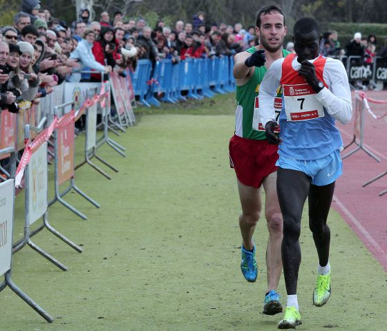 Fernández Anaya helps Mutai toward the line. / CALLEJA (DIARIO DE NAVARRA)