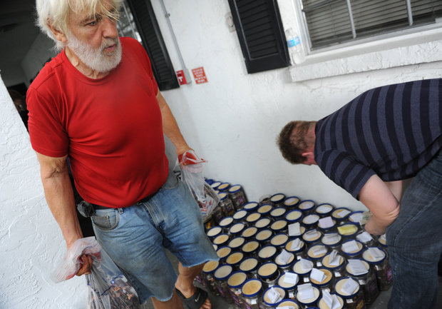 Rick Snyder helps sort and pack more than $21,000 in coins and bills he has collected over the past 10 years to donate to the Gulf Shore Animal League.
