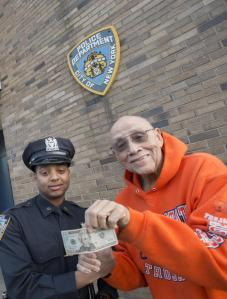 Lemuel (Bill) Copeland, left, pays back NYPD Officer Marvin Luis the $20 the cop gave him.