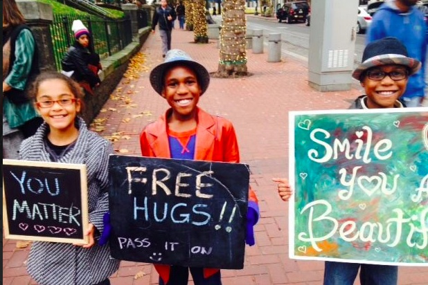 "Devonte Hart, holding a ""Free Hugs"" sign"
