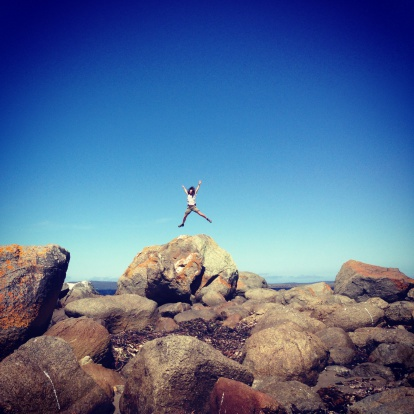 Woman jumping in air from large rock at the beach
