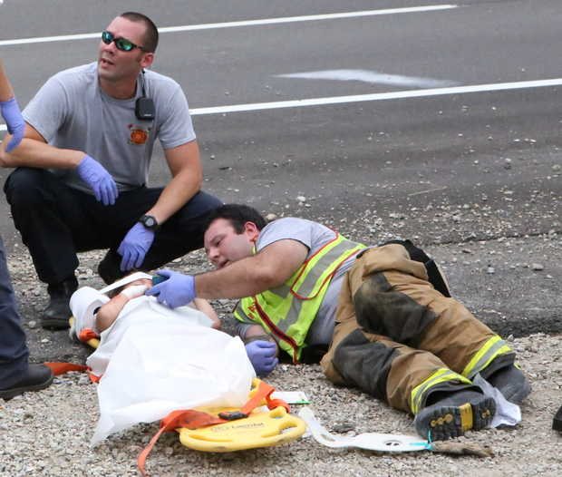 firefighter Casey Lessard, right, plays a cartoon on his cellphone to calm an injured child