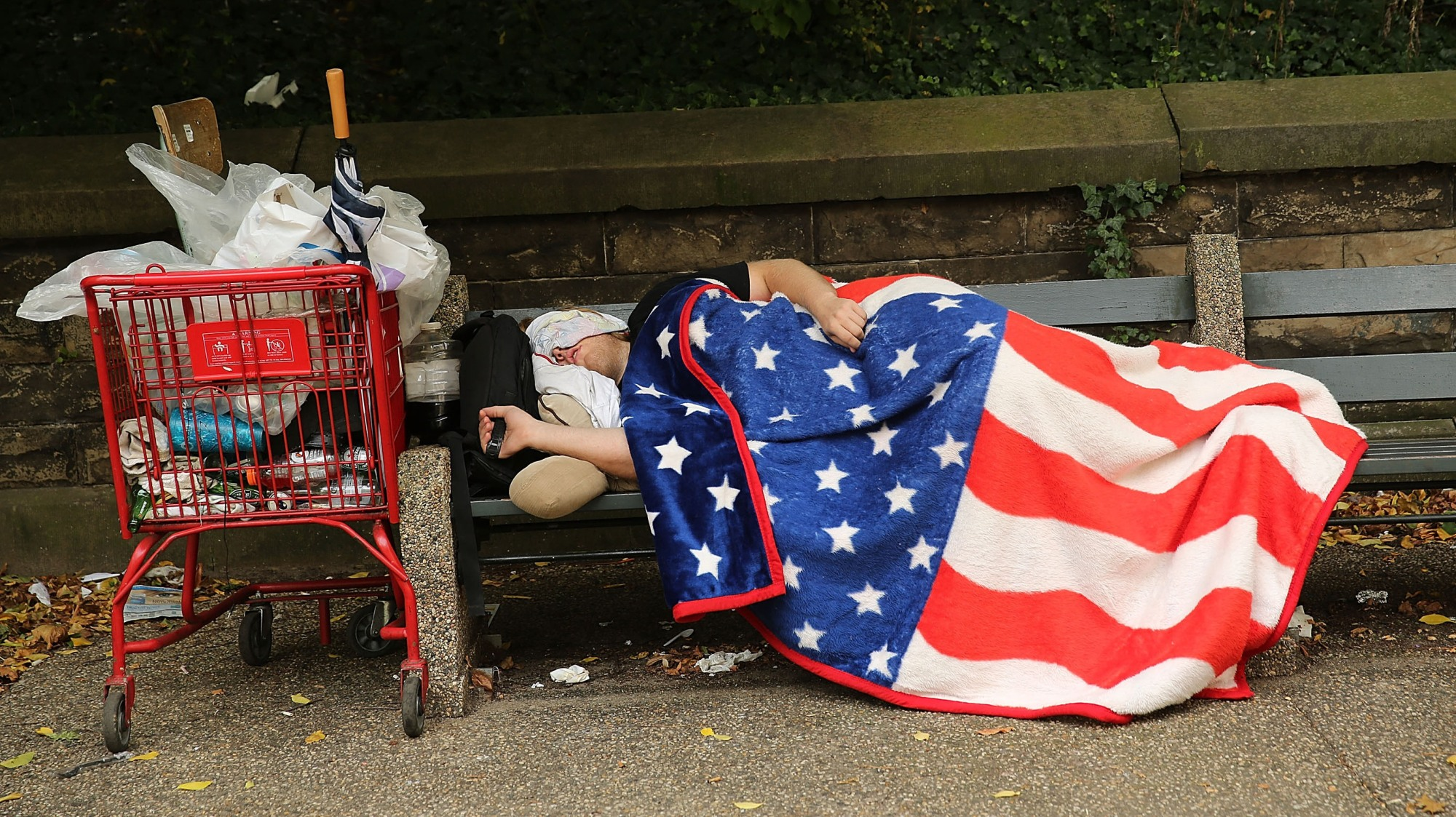 A homeless man sleeps under an American flag blanket