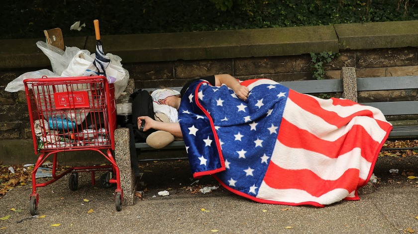 A homeless man sleeps under an American flag blanket
