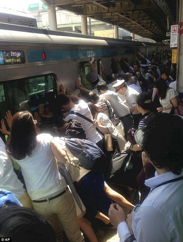 A train station full of people push against a train to help rescue someone who fell in the gap.