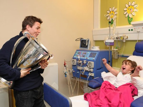 Irish rugby player Brian O'Driscoll visiting a young girl in the hospital after winning the Heineken cup.