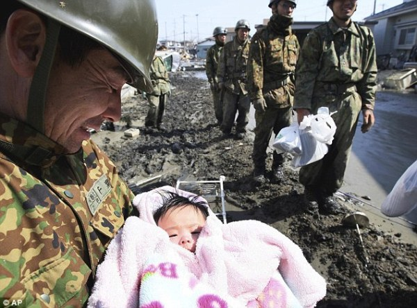 Japanese rescue worker pulled a baby (unharmed) out of the rubble after the 2011 earthquake/tsunami. I love the smile on his face.