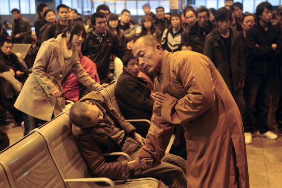 An elderly person passed away in the waiting hall of the Shanxi Taiyuan train station, China. A monk who happened to be waiting for his train went forth, held the deceased's hand, and proceeded to bless him.