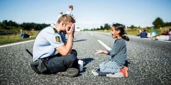 This picture of a danish police officer, playing with a syrian refugee, on the highway.