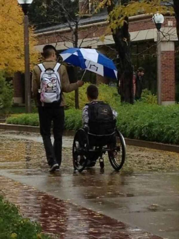 This picture of a man holding an umbrella over a guy in a wheelchair.