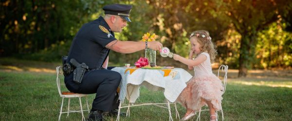 Little girl has tea party with police officer who saved her life after she choked on a coin