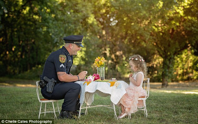 Tea for two: Police Corporal Patrick Ray, from Rowlett, Texas, is pictured at a tea party with 2-year-old Bexley Norvell whose life he saved a year ago