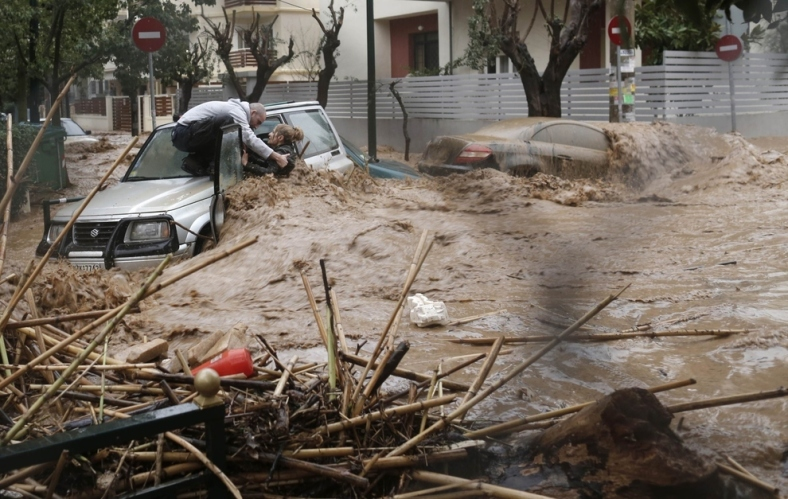 A man rescues a woman from her car on a flooded road in the Athens suburb of Chalandri in February.